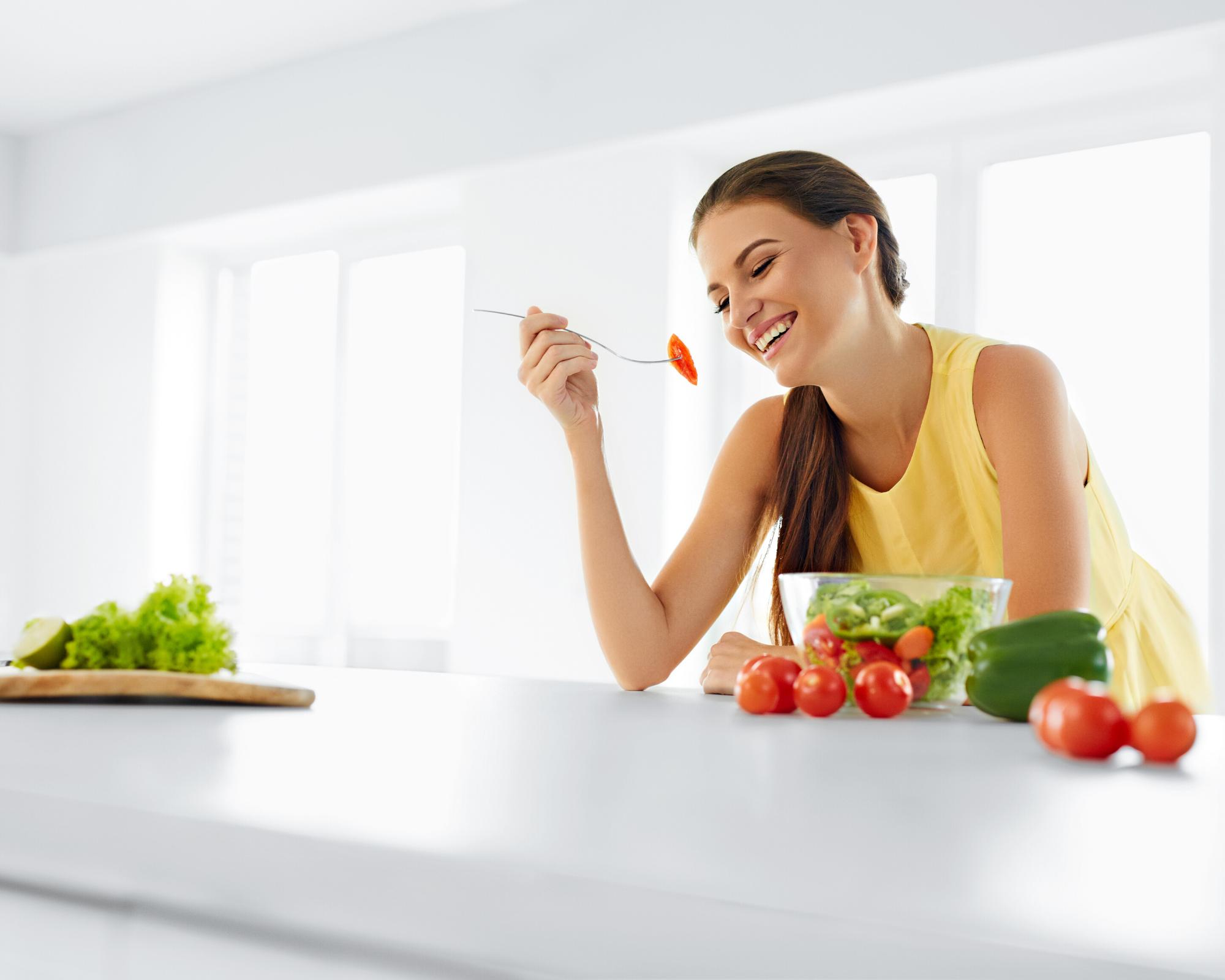 Women smiling as she enjoys her salad.