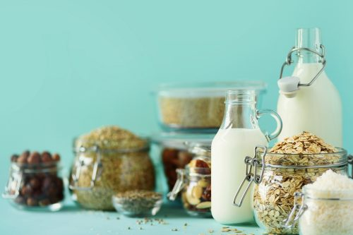 Jugs filled with grains, DF milk & nuts suitable for GF & DF Mediterranean Style Meal Plan.