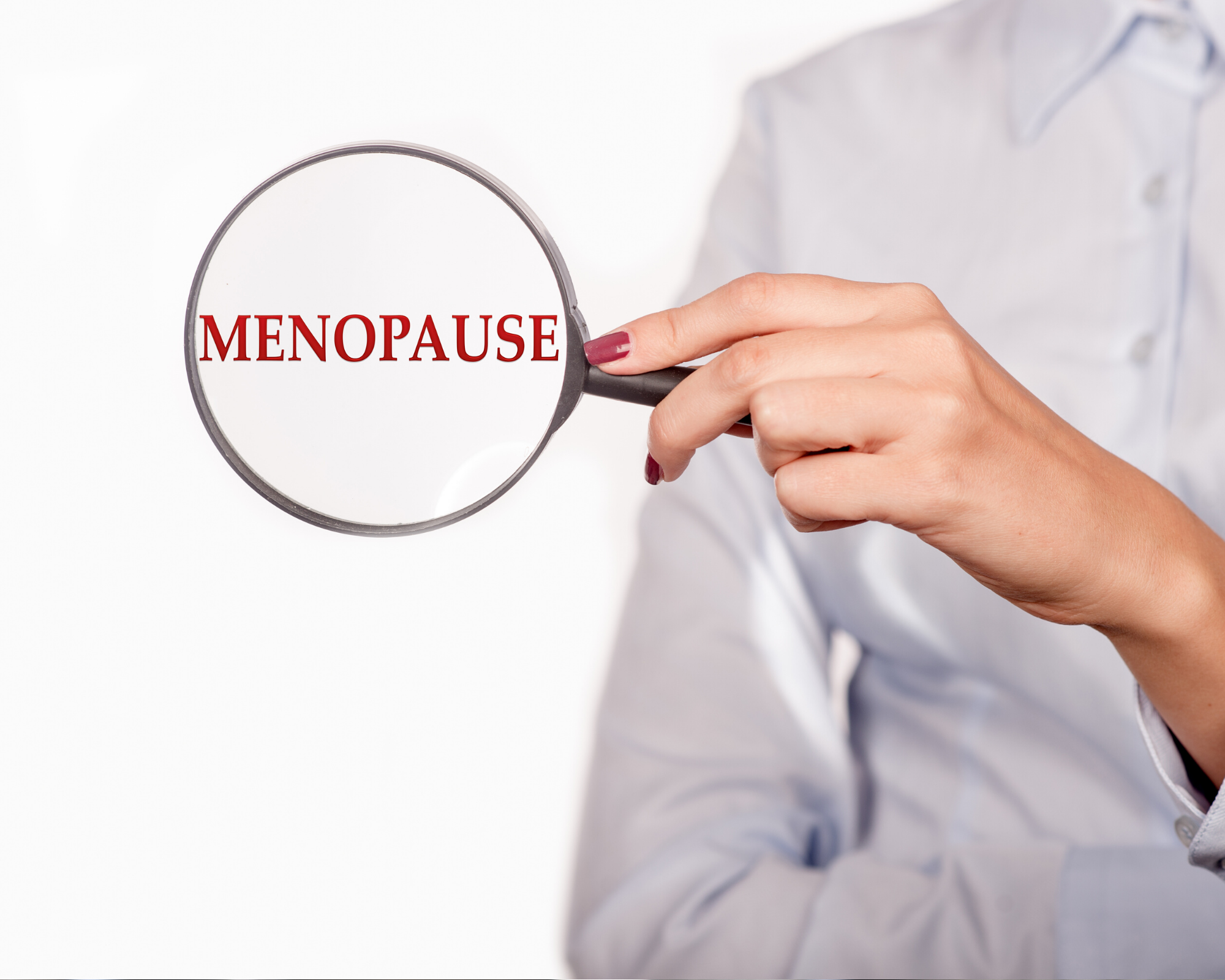 """Women holding a magnifying glass over the words """"menopause"""""""